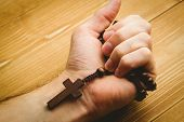 foto of rosary  - Hand holding wooden rosary beads in close up - JPG