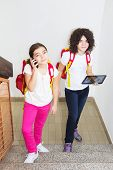 image of ten years old  - Ten year old twin sisters using computer tablet and smart phone - JPG