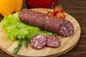 pic of salami  - Sliced Salami with salad leaves on the wood background - JPG