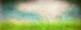 picture of nature conservation  - Concept or conceptual green fresh summer or spring grass field over a blue sky background on a vintage old paper - JPG
