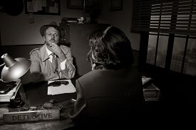 picture of 1950s style  - Handsome detective at office desk interviewing a young woman 1950s film noir style - JPG