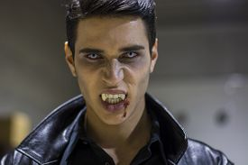 picture of scary face  - Close up Face of a Handsome Vampire Man in Leather Clothing with Blood on his Mouth Looking at the Camera - JPG