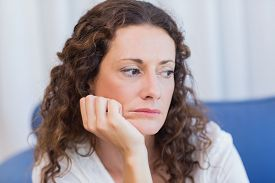 picture of couch  - Worried woman sitting on the couch in the living room - JPG