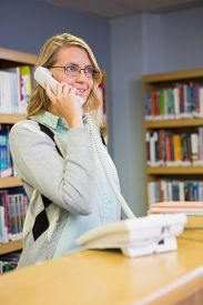 image of librarian  - Pretty librarian answering the phone at the university - JPG
