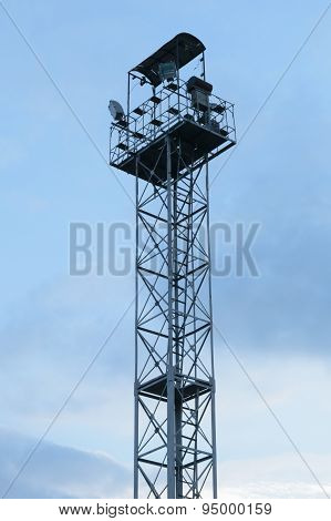 High Lighting Tower With Observation Platform At The Top Against A Blue Sky With Clouds