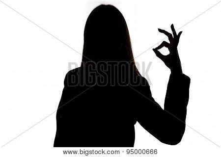 Silhouette of woman showing okay