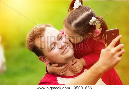 Little Girl Kissing Her Father On Cheek While Taking Selfie