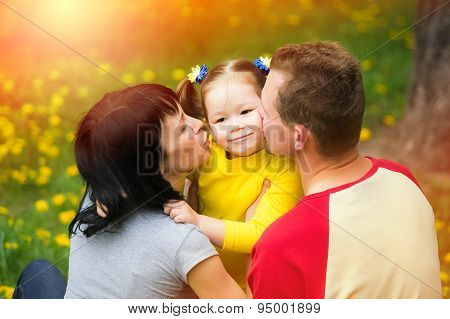 Mum And Dad Kissing Cheeks Of Daughter
