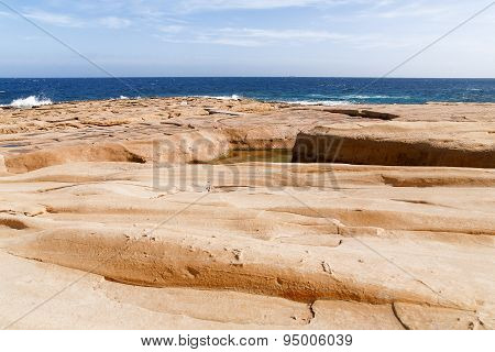 The Waves Beat Against The Rocky Shore. Water Flooded Depressions In The Rocks. Malta, Saint Julians