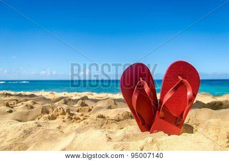 Red Flip Flops In Heart Shape On The Sandy Beach