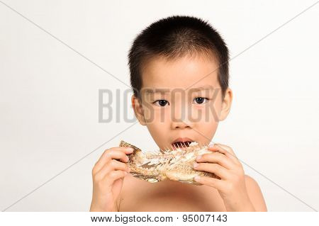 Young Asian Boy Eating Fish