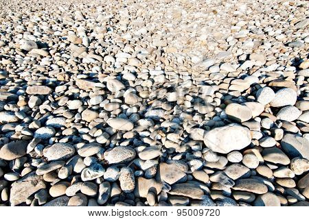 Slightly Blurred Image Of Bed Of Dried River Rocks For Background Purposes.