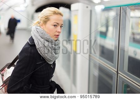 Young woman on platform of metro station.