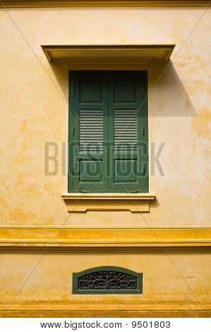 Green Window Shutters On Yellow Wall With Great Shadows