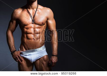 Muscular and sexy torso of young man with perfect body in panties