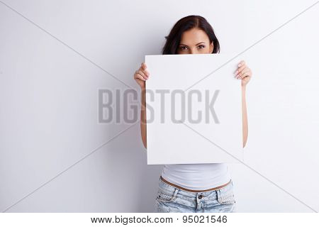 Beautiful healthy woman is presenting some empty picture
