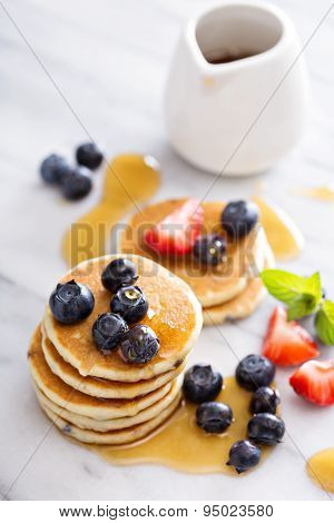 Stack of small pancakes with berries
