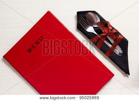 Silverware With Red Bow On Black Napkin Next To Menu