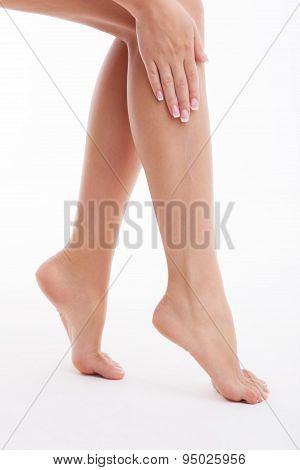 Healthy girl is applying cream on her feet