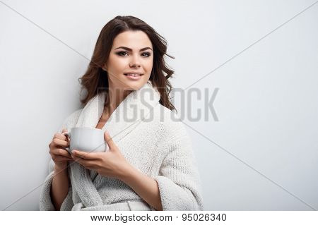 Beautiful young woman is drinking hot coffee