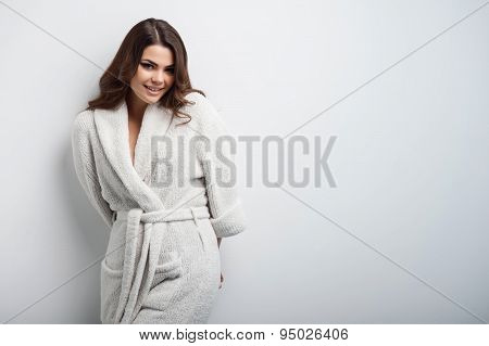 Beautiful young girl is standing in bathrobe