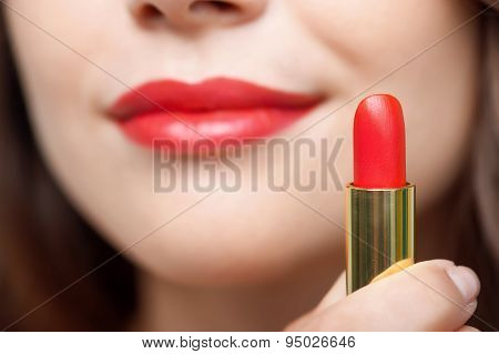 Pretty young woman is after rouging her lips