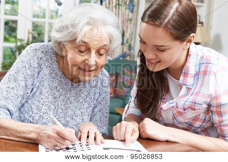 Teenage Granddaughter Helping Grandmother With Crossword Puzzle