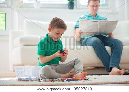 Little Boy Play , Father Read Newspaper