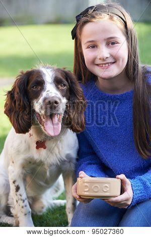 Girl Feeding Pet Spaniel Dog From Bowl Outdoors In Garden