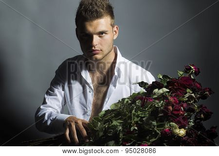 Portrait Of Handsome Man With Flowers In Studio