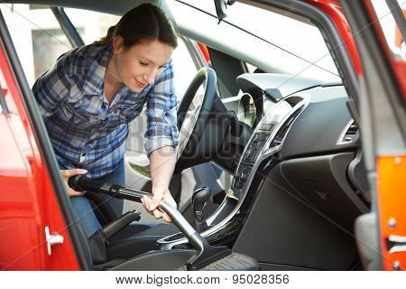 Woman Cleaning Interior Of Car Using Vacuum Cleaner