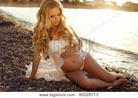 Beautiful Pregnant Woman With Long Blond Hair Posing On Sunset Beach