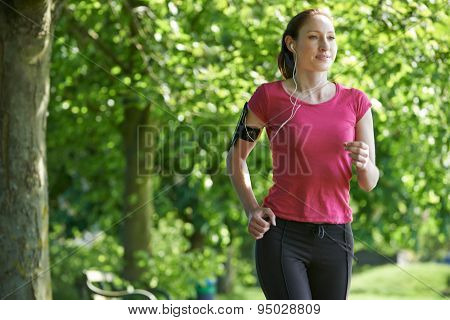 Female Runner In Park With Wearable Technology