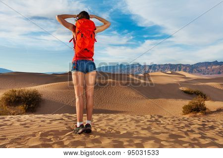 Girl wears rucksack, stands with Death valley view