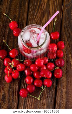 Top View On Ice Cubes In Jar And Cherries Around