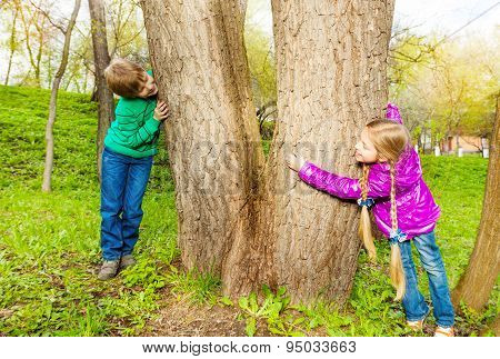 Boy and girl playing hide-and-seek in the forest