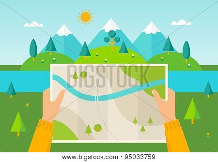 Man on a hiking trip holding a map in his hands. Nature landscape of mountains, hills, meadows and r