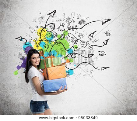 A Brunette Woman Is Holding Three Colourful Gift Boxes. Drawn Sketch On The Wall With Arrows And Sho