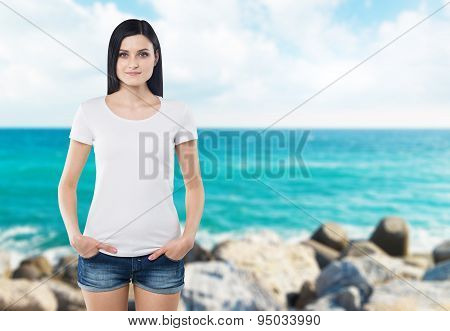 Close-up Of A Woman In A White T-shirt. Hands In The Pockets Of Denim Shorts. Blur Sea View.