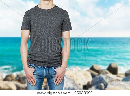 Close-up Of A Man In A Blank Grey T-shirt. Hands In The Denims Pockets. Blur Sea View.
