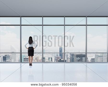 Rear View Of Brunette Woman In The Office Who Looks Through The Window. New York Panoramic Office. A
