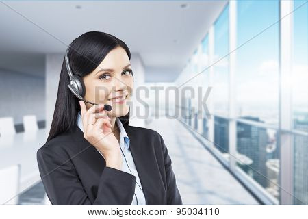 Portrait Of Smiling Cheerful Support Phone Operator In Headset. Modern Panoramic Office.