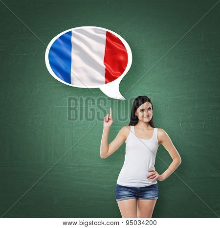 Beautiful Woman Is Pointing Out The Thought Bubble With French Flag. Green Chalk Board Background.