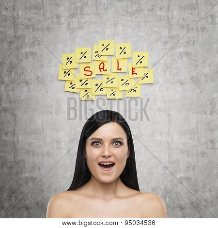Portrait Of An Astonished Brunette Girl. Yellow Stickers With The Word ' Sale ' Are Hanged On The Co