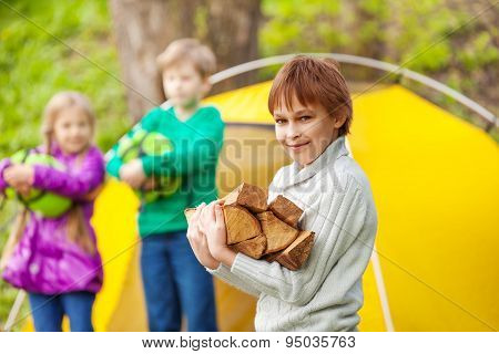 Boy holds the wood for bonfire during camping