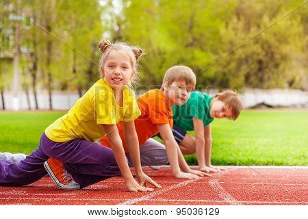 Children stand with bended knee ready to run