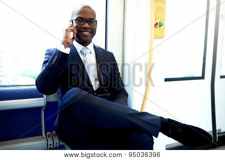 Happy Businessman In A Train Calling On Phone