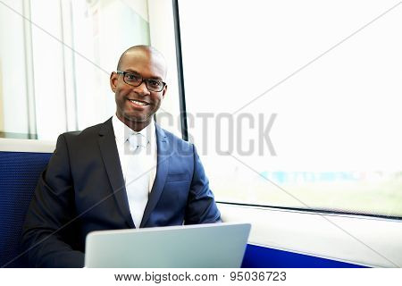Smiling Businessman With Laptop Commuting On Train