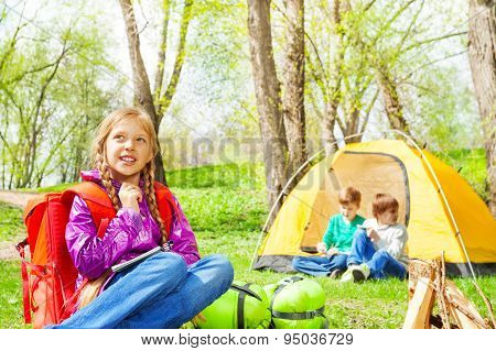 Looking girl with red backpack rests in camp