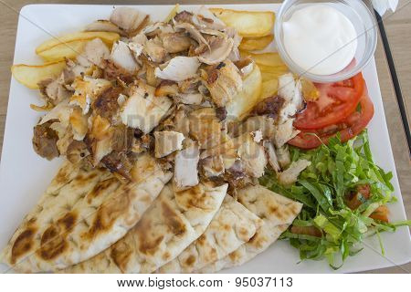 Chicken Gyros Portion  With Vegetables Served On A Plate